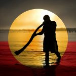 Aboriginal Playing Didgeridoo at Sunrise